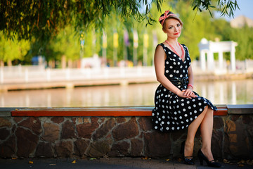 A beautiful young woman dressed sits on a bench near the pond