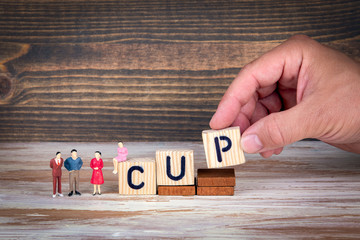 cup. Sports competitions, success at work or achievements in training. Wooden letters on the office desk, informative and communication background