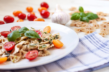 White plate with farfalle aglio olio, cherry tomatoes, fresh basil and garlic