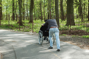 A man carries a disabled person in a wheelchair up the hill.