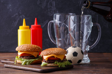 Photo of two hamburgers, glasses, soccer ball, ketchup