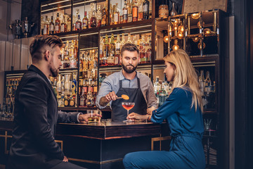 Stylish brutal barman serves an attractive couple who spend an evening on a date. Wall mural