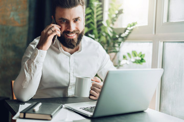 Young smiling bearded businessman is sitting at table in front of laptop, drinking coffee, talking on cell phone. Telephone conversations, remote work, online training, education, marketing, working.
