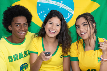 Three brazilian fans watching match of Brazil live at tv