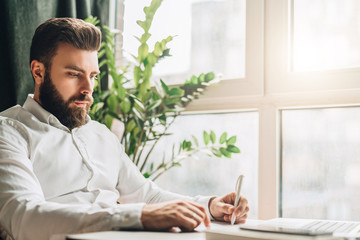 Young bearded businessman is sitting at table in office in front of laptop near window and writing in notebook. Man takes notes in a notepad. Distance work, online marketing, education, e-learning.