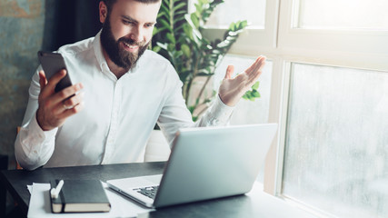 Young bearded businessman in a white shirt is sitting at a table in front of a laptopand is happily looking at the computer screen, raising his hands up. Victory, growth of indicators, good news.