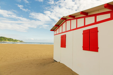 white summer house with red shutters against the backdrop of the sea. Summer seascape with a dwelling and a sea horizon.