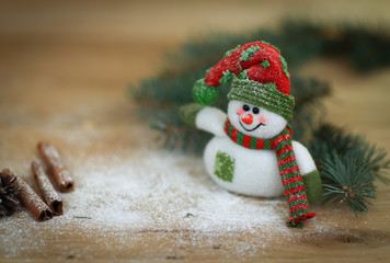 Christmas Cup and a toy snowman on wooden background