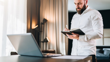 Young serious bearded businessman stands near desk opposite laptop and makes notes in notebook. Student is studying online. Freelancer works at home. Online marketing, education, e-learning, work.