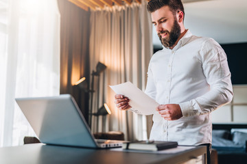 Young bearded businessman in white shirt is standing near desk in front of laptop, reading documents. Freelancer working home. Student learning online. Online marketing, education, e-learning.