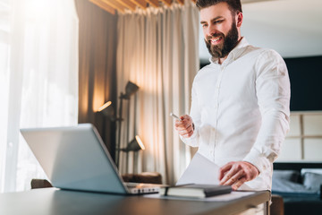 Young bearded smiling businessman in white shirt is standing near desk in front of laptop, holding in his hand documents, pen, looking at computer screen. Distance work, freelancer working home.