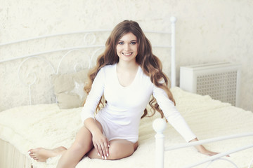 Young attractive woman with beautiful long wavy hair in bodysuit sitting on the bed.