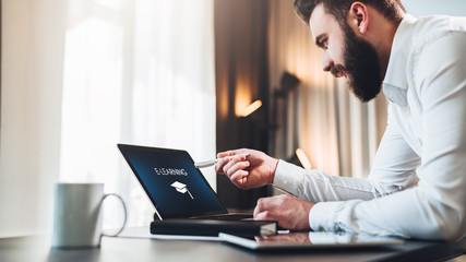 Young bearded businessman in white shirt is sitting at table in front of computer,pointing with pen on laptop screen.On monitor inscription e-learning and image of square academic cap.Online education