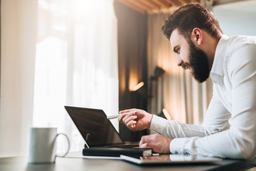 Young bearded businessman in white shirt is sitting at table in front of computer, showing pen on laptop screen. Freelancer working home. Online education, marketing, e-learning. Business planning.