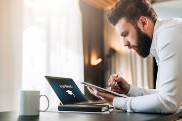 Young bearded businessman sitting at desk in front of laptop with an inscription e-learning on screen, making notes in tablet computer. Freelancer works. Student learning online. Online marketing.