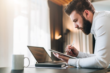 Young bearded businessman in shirt sitting at desk in front of laptop, making notes in digital tablet. Freelancer works remotely. Student learning online. Online marketing, education, e-learning.