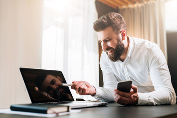 Young bearded businessman in white shirt sitting at table in front of computer, showing pen on laptop screen, holding smartphone. Online education,marketing, e-learning. Business planning, e-commerce.