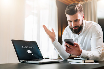 Young bearded businessman in a white shirt is sitting at a table in front of a laptop with an incription e-learning on screen and is happily looking at screen of smartphone, raising his hands up.