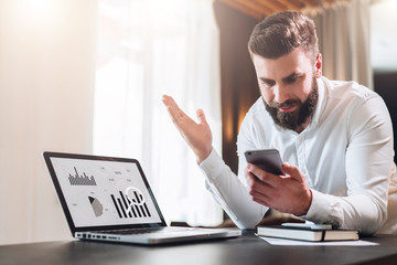 Young bearded businessman in white shirt is sitting at table in front of laptop with graphs, charts, diagrams on screen and is happily looking at screen of smartphone, raising his hands up.