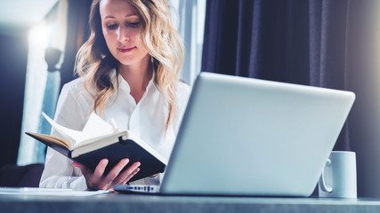 Young businesswoman in shirt is sits in office at table in front of computer and reads notes in notebook.Student does homework, girl reads book. Online marketing, education, e-learning, distance work.