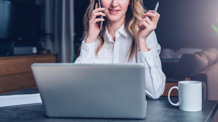 Young businesswoman in shirt is sitting in office at table in front of computer, talking on cell phone, holding pen in her hand. Telephone conversation, online marketing, education, e-learning.