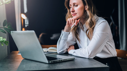 Young businesswoman in white shirt is sitting in office at table in front of computer and pensively looks at screen of laptop, holding pen in her hand. Fatigue from work, sadness. Distance education.