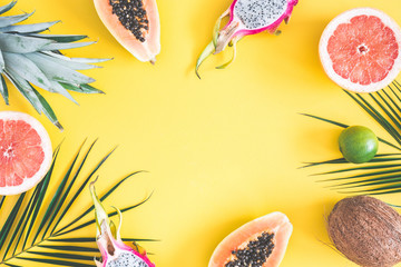 Summer fruits. Tropical palm leaves, pineapple, coconut, papaya, dragon fruit, orange on yellow background. Summer concept. Flat lay, top view, copy space