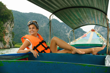 Young woman on the long-tail boat during her vacations in Thailand