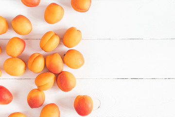 Apricots on white wooden background. Flat lay, top view, copy space
