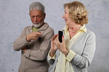 Jealousy concept. Senior couple , jealous husband spying his wife, reading messages on mobile phone