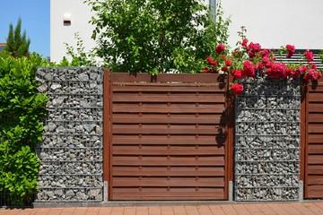 Moderner Sichtschutzzaun aus mit Naturstein gefüllten Gabionen, Holzbretterverschalung und eingegrüntem verzinktem Stahlgitter um ein bebautes Grundstück