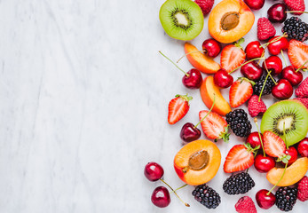 Fresh fruits and berries copy space on marble table top view flat lay.