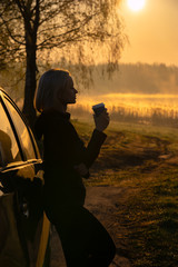 Woman have coffee break near the car at beautiful sunrise on the river