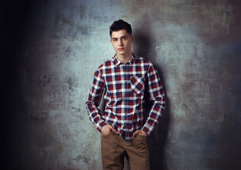 Portrait of young trendy handsome man with short dark hair wearing checkered shirt and brown trousers standing and posing against gray concrete wall