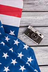 USA flag and vintage camera, top view. National flag of America and retro camera on wooden background. History of America.