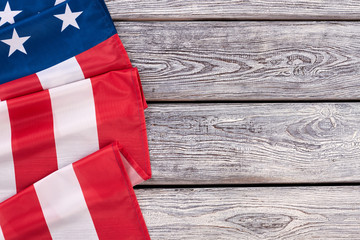Border from American flag, horizontal image. United States of America flag draped as a border with a old wooden background and copy space.