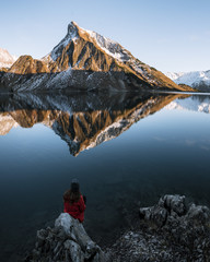 Woman sitting on a rock overlooking a mountain lake with reflection at sunset
