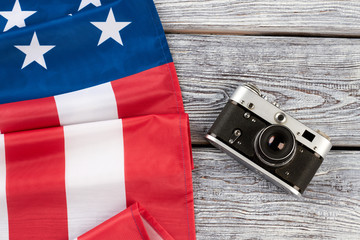 Folded american flag and film camera. USA national flag and old-fashioned camera on rustic wooden background, horizontal image.