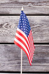 National flag of USA, vertical image. Small flag of United States of America on old wooden background. Symbol of nation and patriotism.