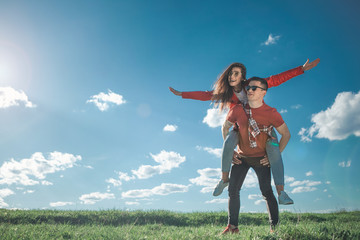 I believe we can fly. Full length of amorous couple looking at blue sky. Girl is on her boyfriend back with stretched arms. They smiling and enjoying summer weather. Copy space in left side Wall mural