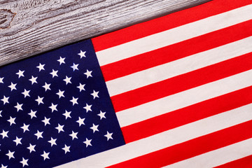 Close up flag of USA on wooden background. Cotton flag of United States of America on grey wood.