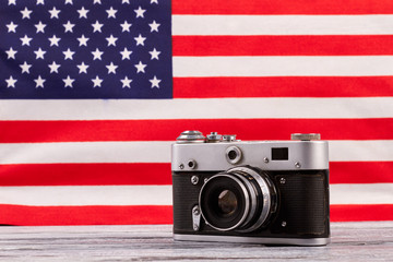 Vintage camera on American flag background. Retro film camera on wooden table with USA flag in the background.