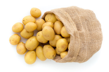 Sack of fresh raw potatoes on wooden background, top view