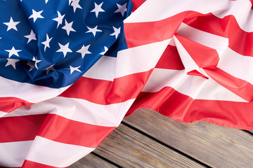 Close up crumpled flag of the USA. National flag of United States of America on light wooden background.