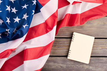 Flag of USA and opened notebook. Top view on flag of United States of America and notepad on wooden background, horizontal image.