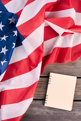 USA flag and opened notebook, top view. Flag of America and personal organizer book on wooden background, vertical image.