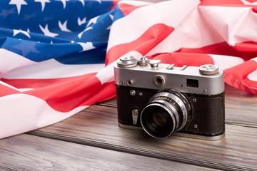 Retro camera and USA flag. Old film camera and American flag on wooden background close up.