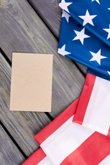 USA flag and craft envelope, top view. Flag of United States of America and brown envelope on wooden background, vertical image.