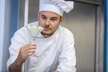 young chef looking as it has been a dessert decoration