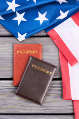 Two passports and American flag. Top view on folded USA flag and personal documents on wooden background, vertical image.